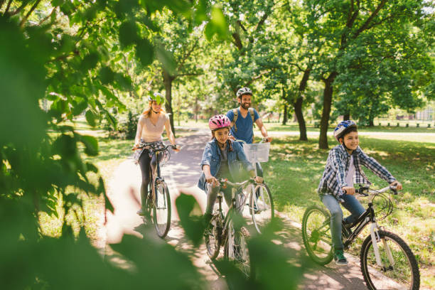 family riding bicycle - public park stock photos and pictures