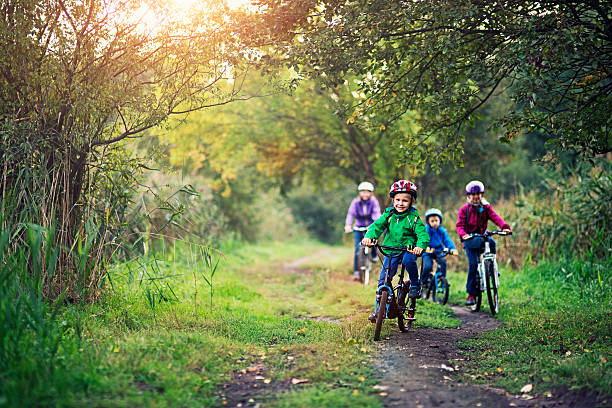 familie reiten fahrräder in wunderschönen natur - kinderfahrrad stock-fotos und bilder