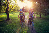Little boy and his family riding bicycles in park. The boy is smiling happily.\nNikon D810