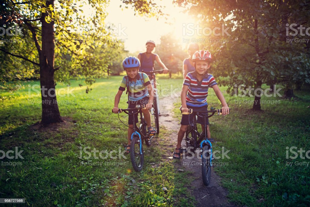 Family riding bicycles in park stock photo