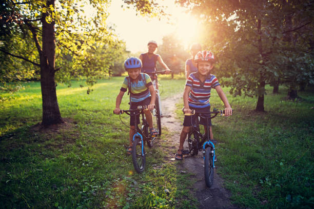 Family riding bicycles in park - foto stock