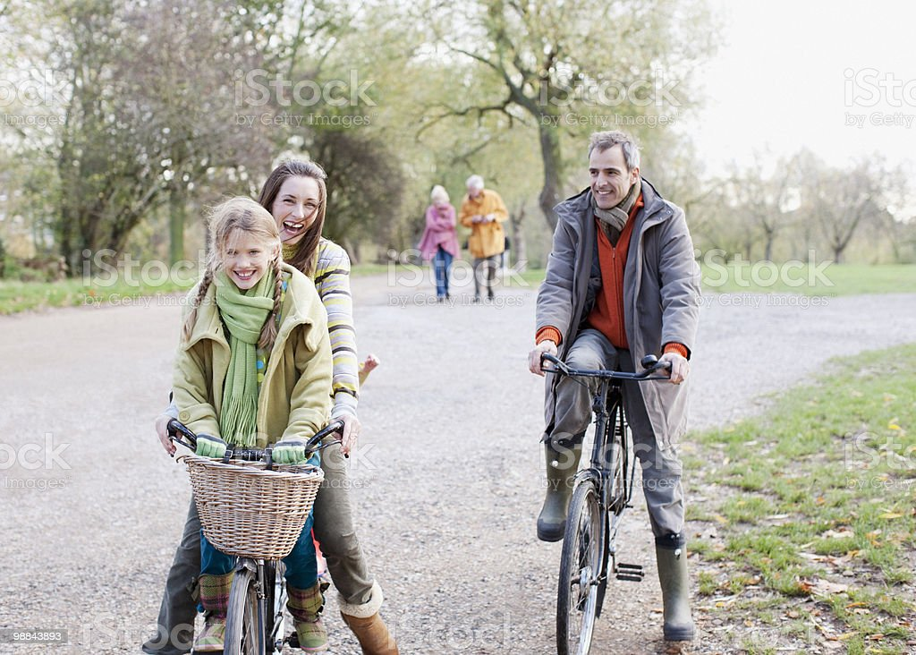 Family riding bicycles in park 免版稅 stock photo