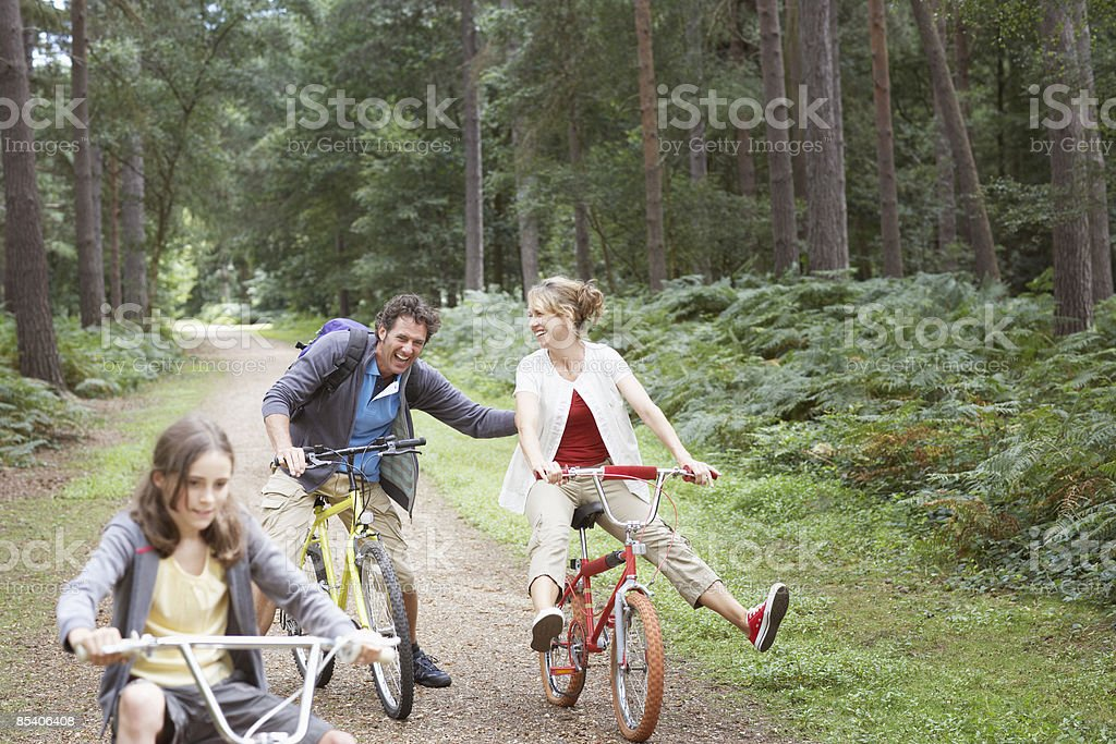 Family riding bicycles in woods stock photo