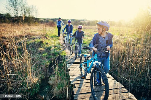969439086 istock photo Family riding bicycles on early spring day 1199610135