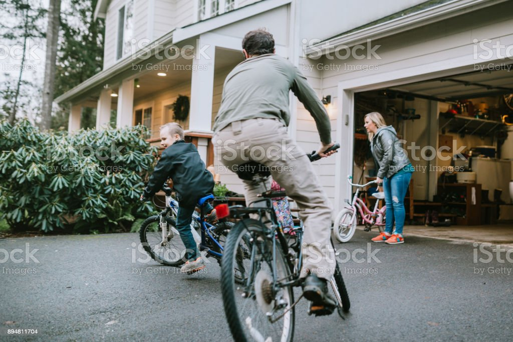 Family Riding Bikes in Home Driveway stock photo