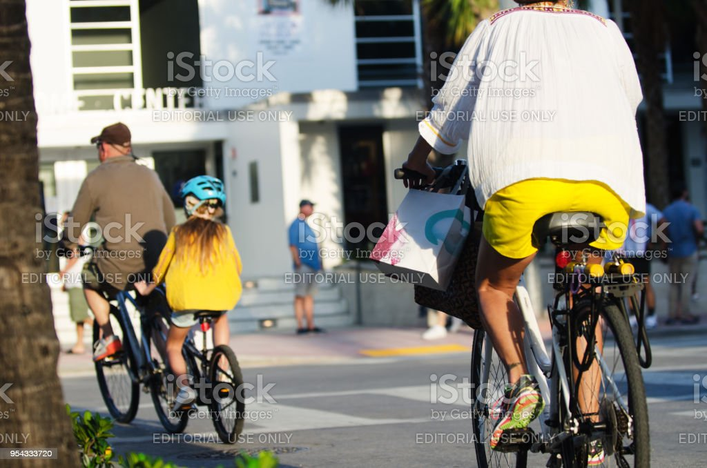 Family Riding Bikes Ocean Drive in South Beach Miami Miami - April 28, 2018: A daughter rides on a tandem bicycle in front of her mother on Ocean Drive in South Beach. American Culture Stock Photo