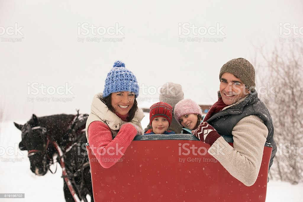 Family riding in horse drawn sleigh stock photo