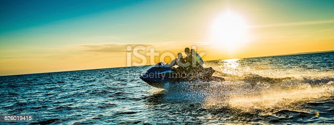 Panoramic shot of family having fun riding a water scooter on the sea at the sunset.