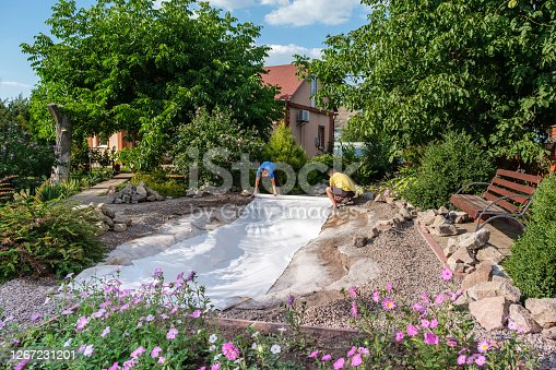 Family roll out a roll of white non-woven geotextile fabric on the ground to set up a fish pond in their backyard near their home.