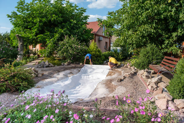 Family roll out a roll of white non-woven geotextile fabric to set up fish pond Family roll out a roll of white non-woven geotextile fabric on the ground to set up a fish pond in their backyard near their home. pond stock pictures, royalty-free photos & images
