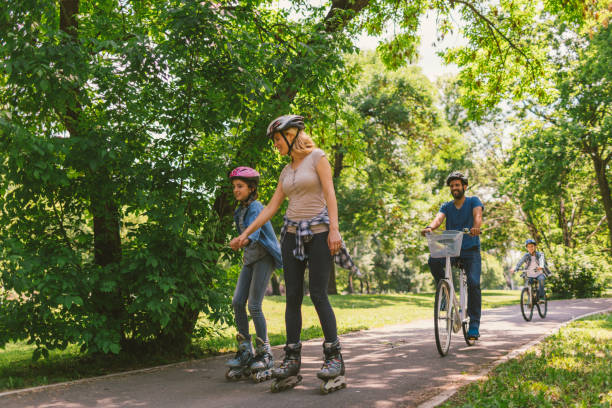 Family roller skating and riding bicycle stock photo