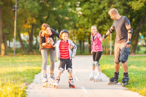Family rollerblading in a park stock photo