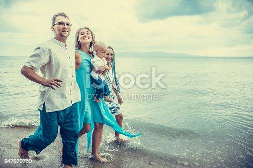 istock Family Running Along Beach 947670750