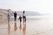 Family Running Along Winter Beach Flying Kite Having Fun