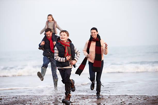 familie winter strand entlang laufen - kinder winterstiefel stock-fotos und bilder