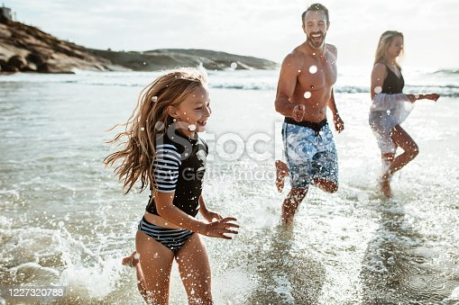 Girl with her parents playing at the beach. Family of three running in the water at the beach.