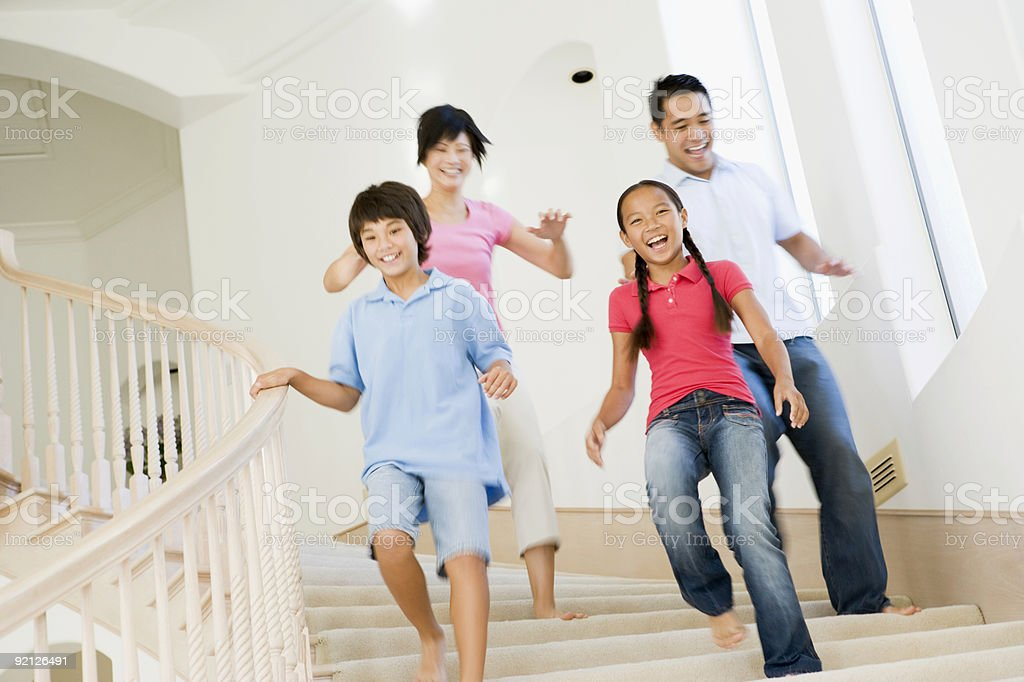 Family running down staircase smiling stock photo