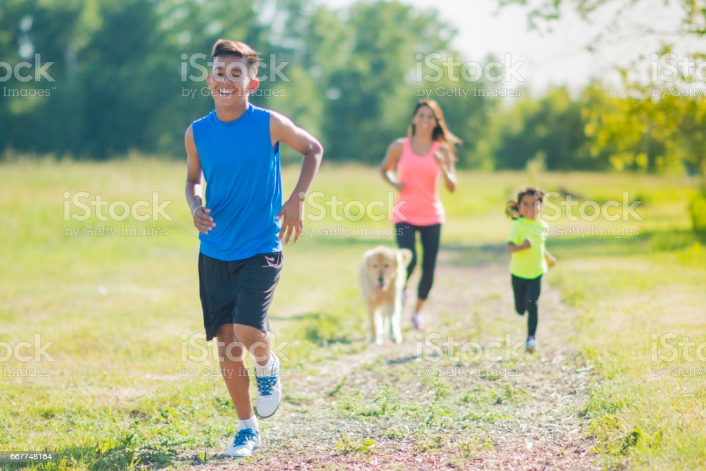 Family Running Following Son With Dog stock photo