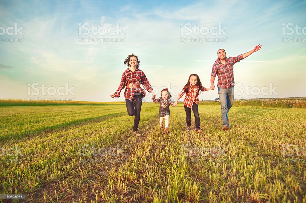 family running in the field. stock photo