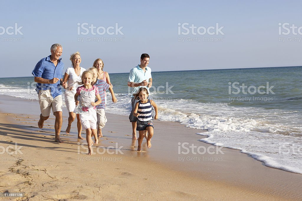 Family running on a beach stock photo