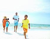 Boy racing family on the beach