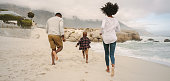 Parents running along beach with son on a vacation. Family running on beach.