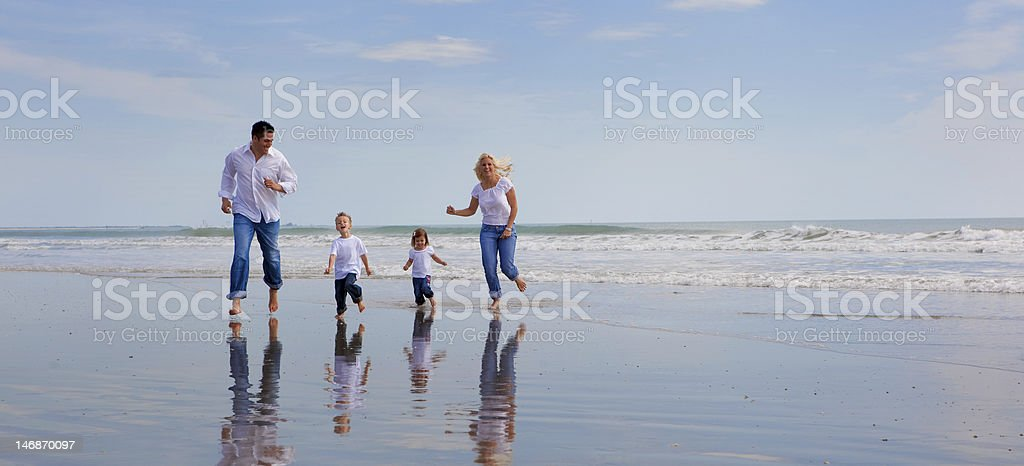 Family running on beach with matching jeans and white shirts royalty-free stock photo