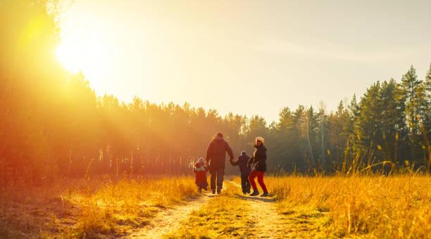 familia corriendo por la carretera del país en el tiempo de otoño - foto de stock