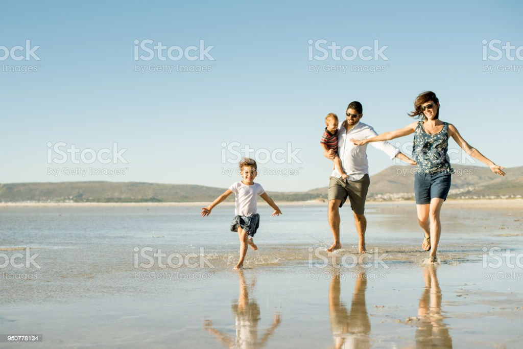 Family running on the beach with their arms outstretched as though they're flying stock photo