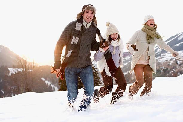 familie läuft im freien im schnee - schneespiele stock-fotos und bilder