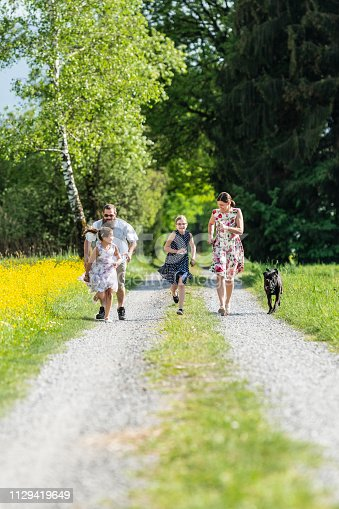 Happy family taking a walk with their dog. The parents are running with their daughters. The bearded father is wearing shorts, the mother and the two daughters summer dresses.