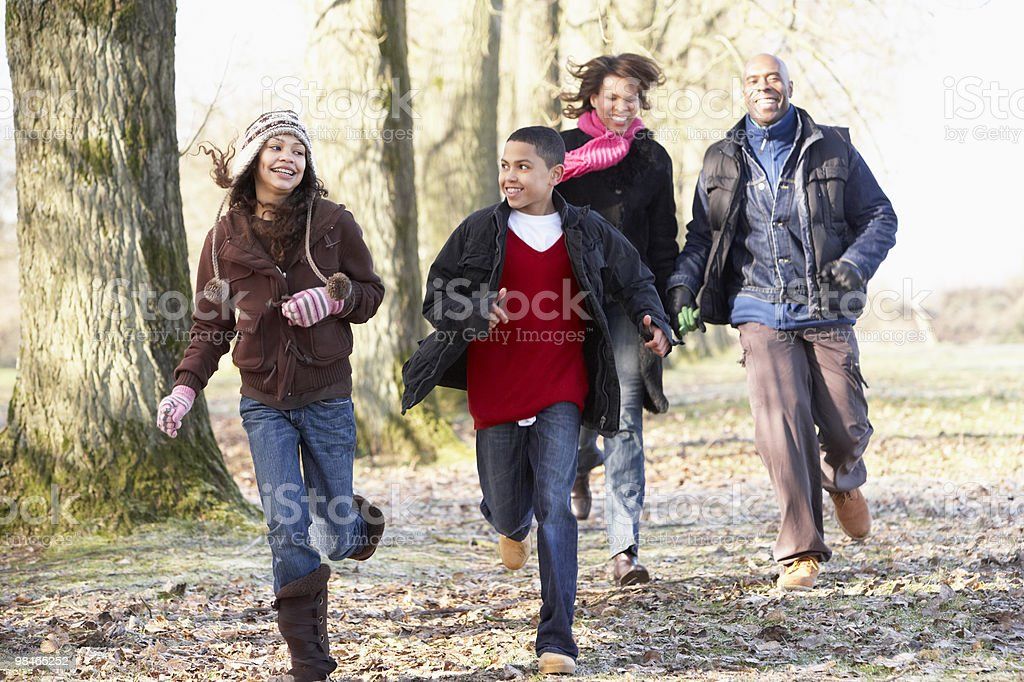 Family Running Through Autumn Countryside royalty-free stock photo