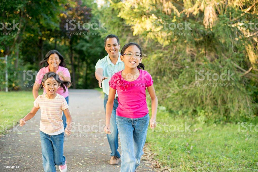 Family Running Through the Park stock photo