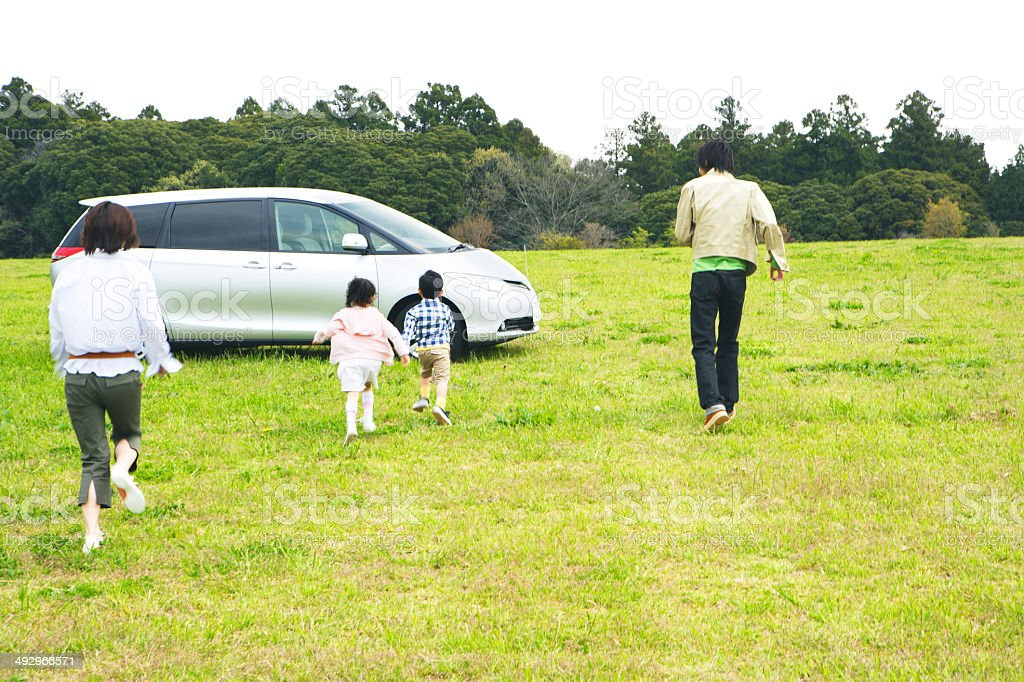 Family running toward car in prairie stock photo