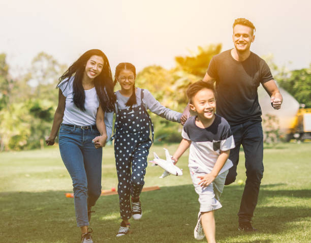 Family running with son and daughter having fun in summer park stock photo