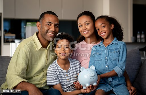 Portrait of a happy African American family saving money in a piggybank and looking at the camera smiling - home finances concepts