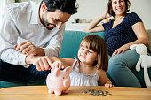 Family saving money in piggy bank