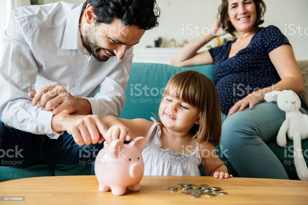 Family saving money in piggy bank stock photo