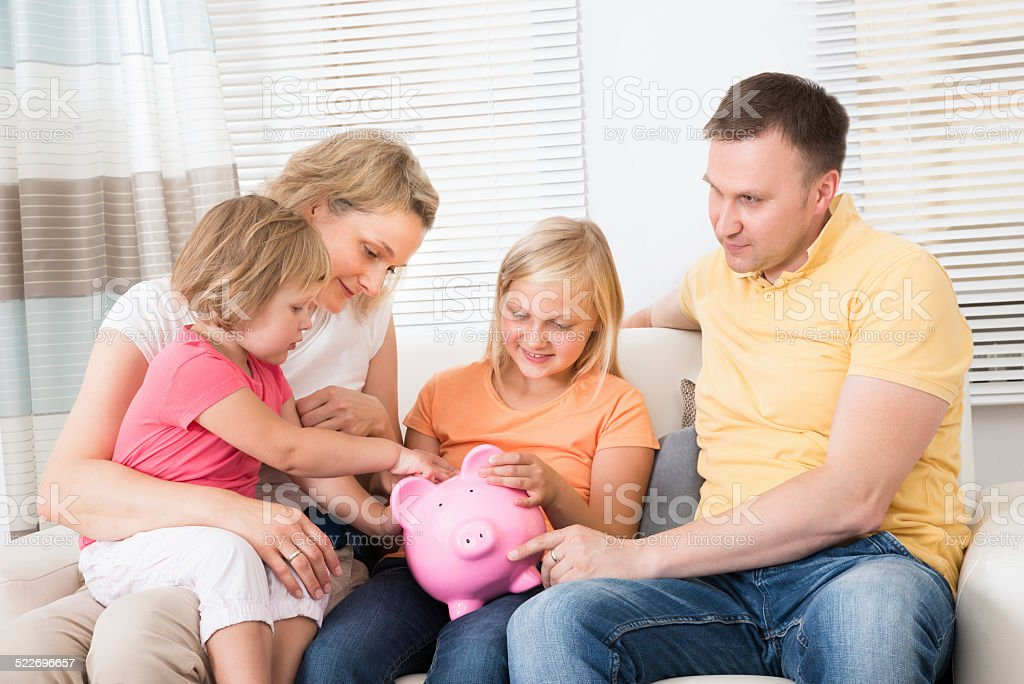Family Saving Money In Piggybank stock photo