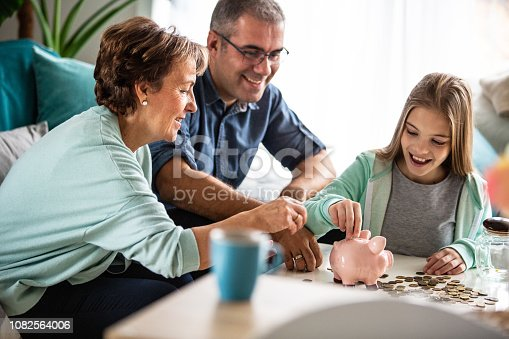 Three generation family is putting coins into piggy bank together.