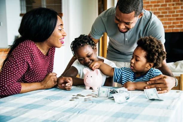 Family saving money to piggy bank stock photo