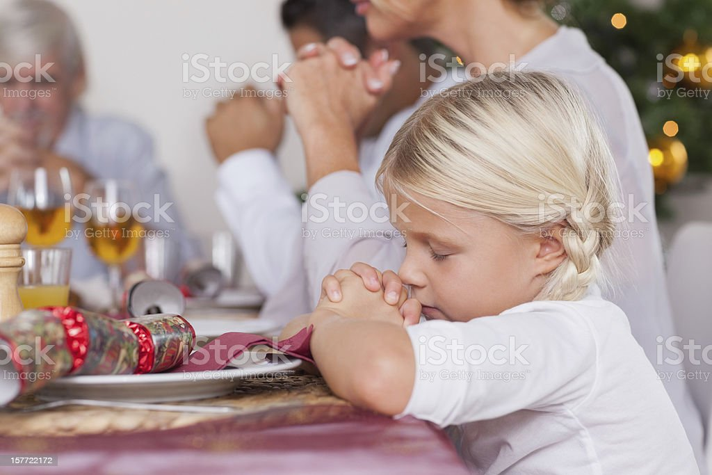 Family saying grace before dinner royalty-free stock photo