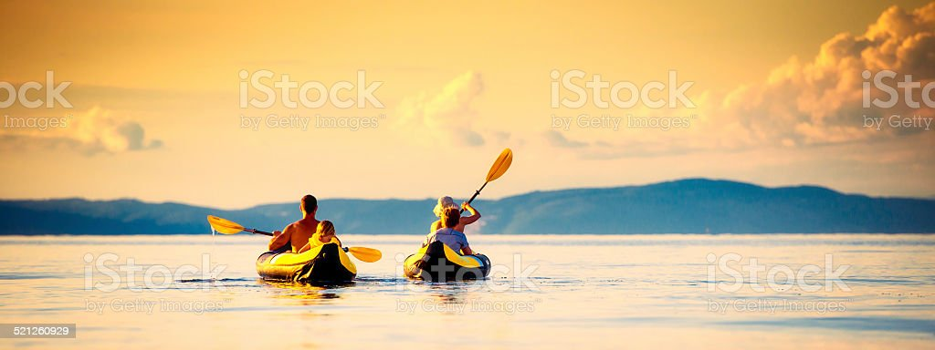 Family Sea Kayaking at Sunset stock photo