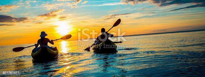 istock Family Sea Kayaking at Sunset 521261411
