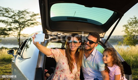 807410214istockphoto Family Selfie while sitting in car trunk 697019818