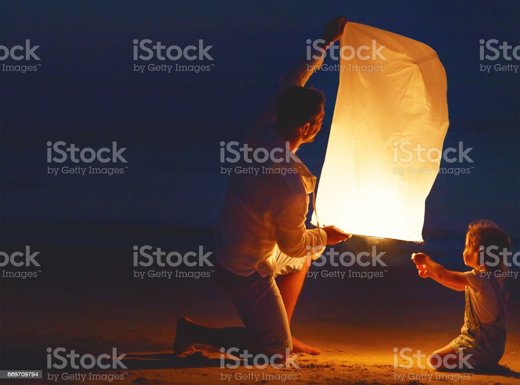 Family send air heavenly flashlight lamp in flight on beach stock photo