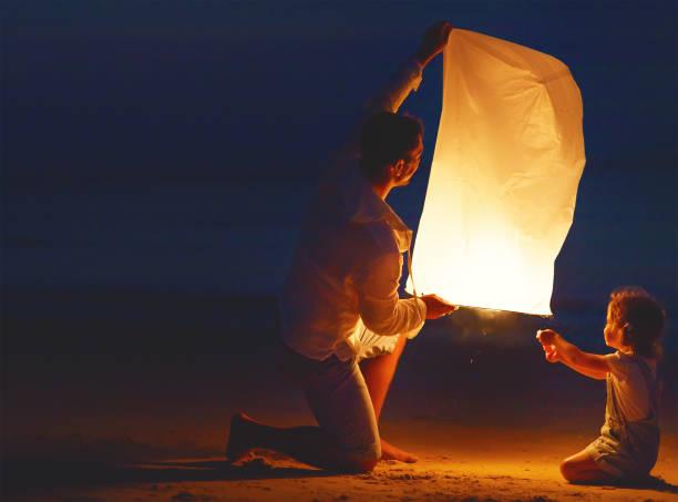 família enviar lâmpada de lanterna celestial de ar em voo na praia - lanterna - fotografias e filmes do acervo