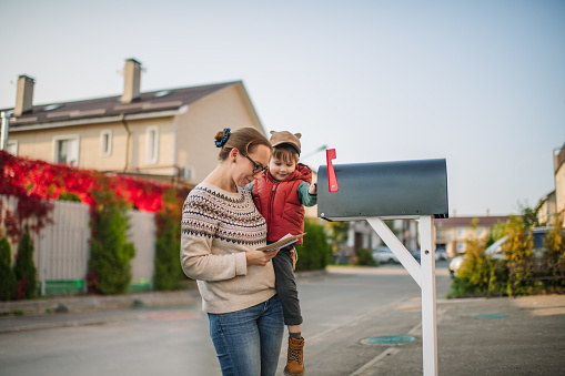 Little boy and his mother on a street with mailbox.