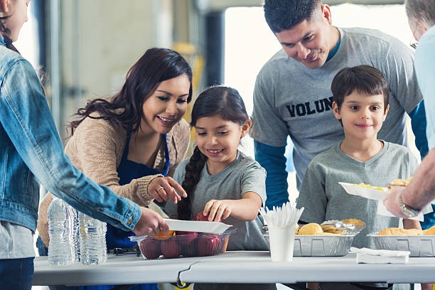 Family serving meals while they volunteer in soup kitchen together stock photo