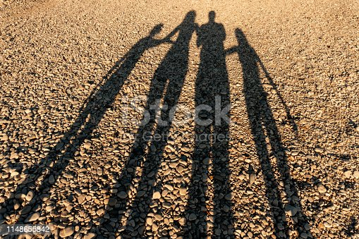 Long shadows of four member family on the beach at sunset. Parent with daughter and son silhouette